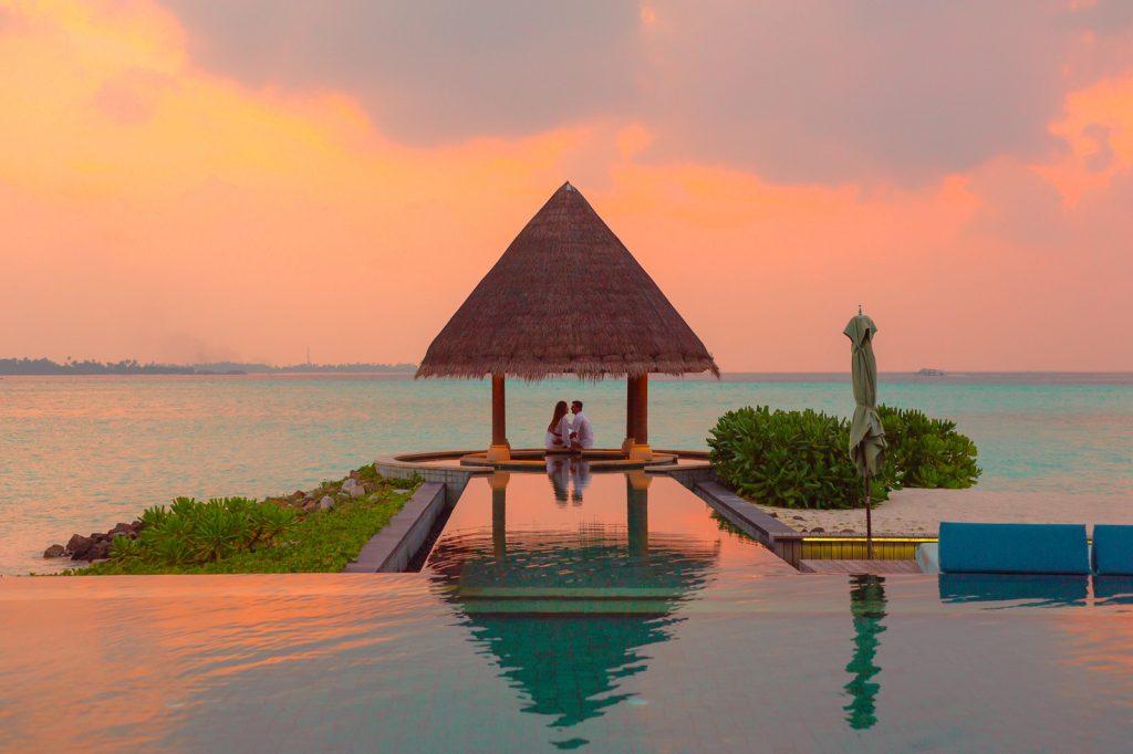 Luxury honeymoon, couple under hut beside sea and infinity pool