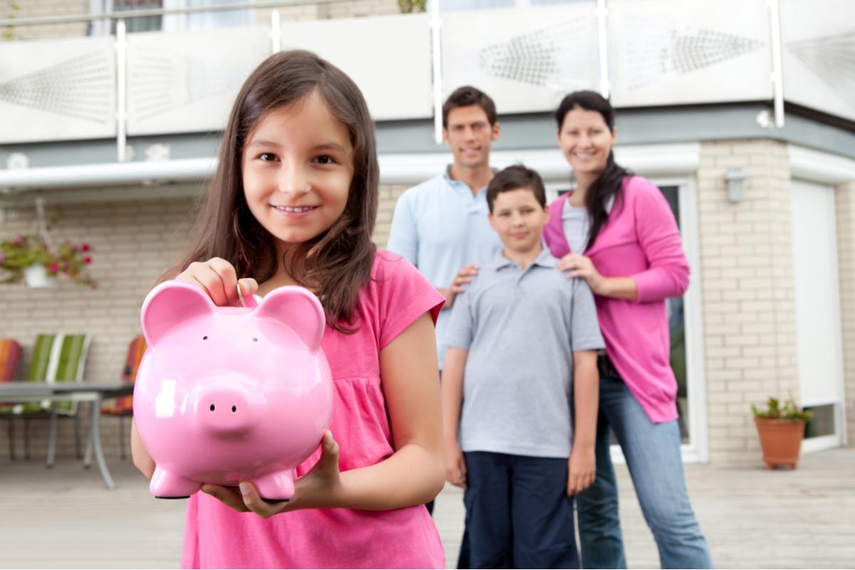 A child holding a piggy bank.