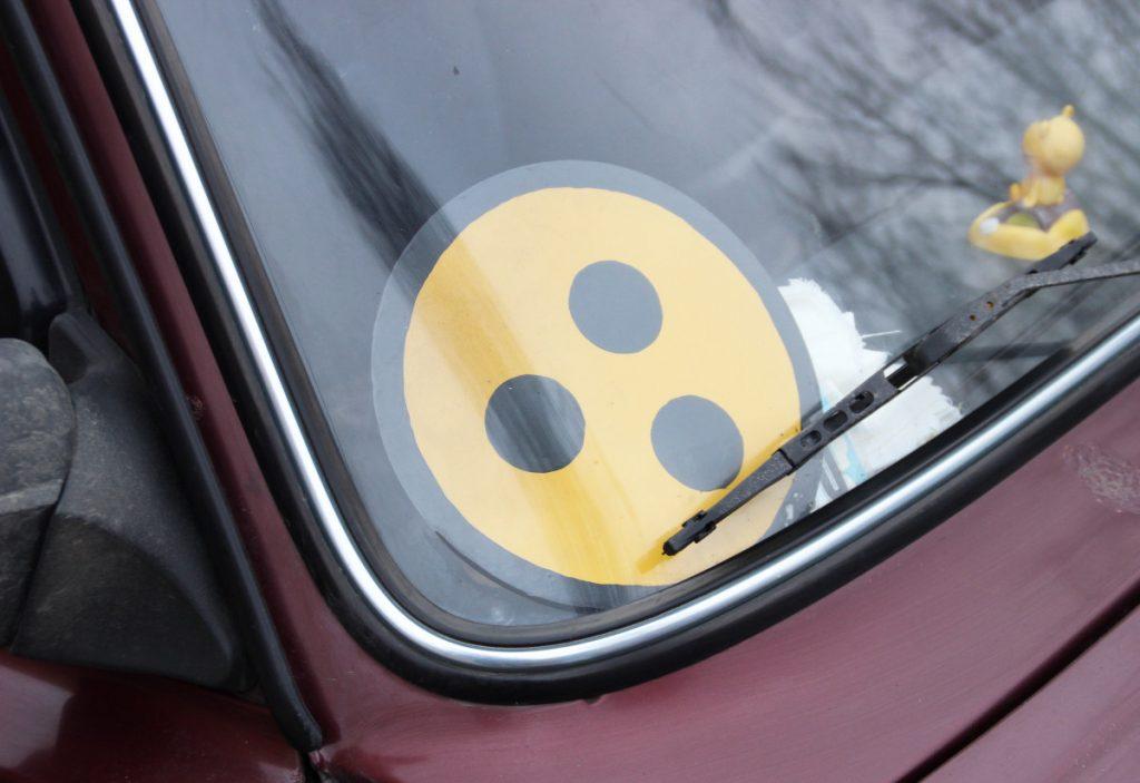 The deaf symbol in a car window.